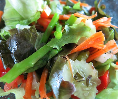 Tasty salad with fresh lettuce leaves, peppers, asparagus , tomatoes, carrots and cucumber with an Italian vinaigrette dressing.