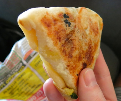 roti pancakes are stuffed with spicy potato curry and served in recycled newspaper or exercise books