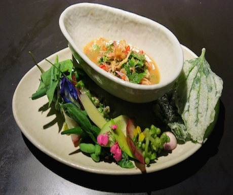 Fresh and spicy dish served with edible flowers at bolan in Bangkok