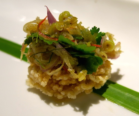 A crispy rice cake topped with local fresh herbs.