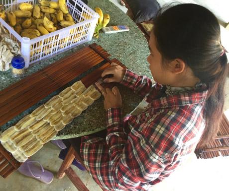 girl drying bananas in Battambang