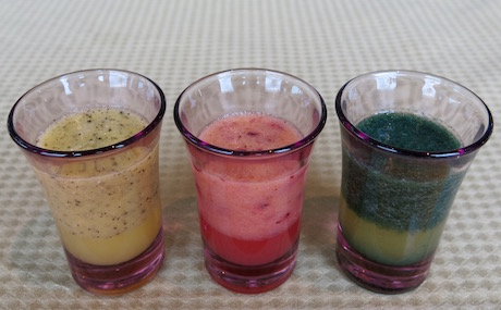 Healthy juice shots including spirulina and melon, banana, dragon fruit and orange and strawberry and orange.