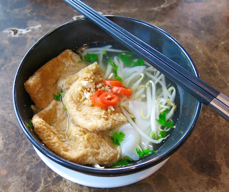 Fresh and tasty vegan noodle and tofu soup for breakfast.