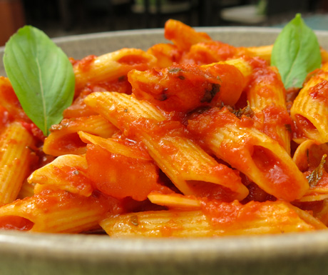 Delicious pasta with fresh tomato sauce and basil leaves.