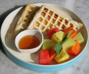 Vegan waffles with fruit salad and palm sugar syrup